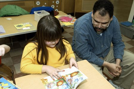MR / Olean, NY / Washington West Elementary School, First Grade Girl (7) reads aloud to visiting adult reading partner from group home. Unique program called Friday Friends pairs adult consumers with special needs with school children. As part of a business-school partnership, consumers and students participate together in reading, crafts, and free time activities. The program's objective is to bring people with and without disabilities together regularly. It is supported by a local, annual fund raising event and hours contributed by volunteers. MR: Sha3   Mon11 © Ellen B. Senisi